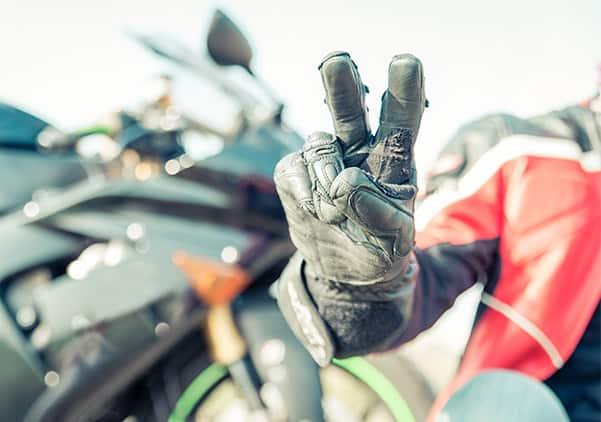 Biker mit Motorradhandschuh zeigt das Peace Zeichen